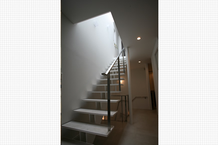 地下から1階への鉄骨階段、吹抜けトップライトで明るい階段